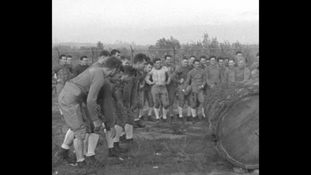 'Class Studies Log Rolling Seattle University of Washington grid warriors train on natural resources' / line of players run behind large log and roll...