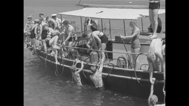 vídeos de stock e filmes b-roll de class studies under water / maybe college students on boat most in swimsuits several on side preparing to go underwater / ms people in water by side... - porta amostra