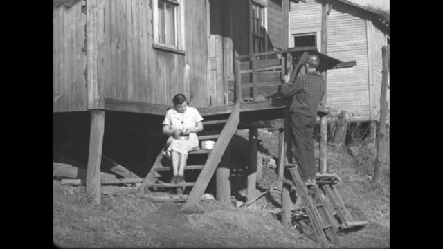 vidéos et rushes de coal aid for miners is federal aim / houses on hillside / ms car drives up road past miners' houses / ms woman sits on porch steps peeling potatoes... - mineur de charbon