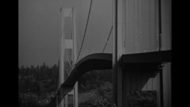 """""""collapse - actual films show tacoma bridge fall"""" / the wide view of the bridge in the distance // opening of the tacoma narrows bridge on july 1,... - puget sound stock videos & royalty-free footage"""