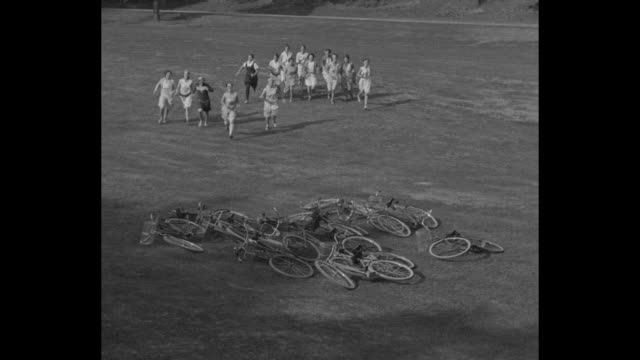"""""""college girls get bike craze, wellesley, mass -- society buds form bicycle brigade to speed to class"""" / group of female students run towards bikes... - 1920 1929 stock-videos und b-roll-filmmaterial"""