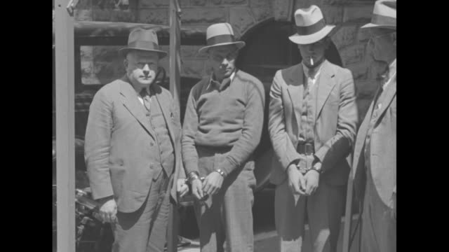 """stockvideo's en b-roll-footage met """"convicts captured in ohio!"""" / pan ext side of jail building / two convicts wearing handcuffs, vernon taylor and henry hopkins, standing between two... - pistool handwapen"""