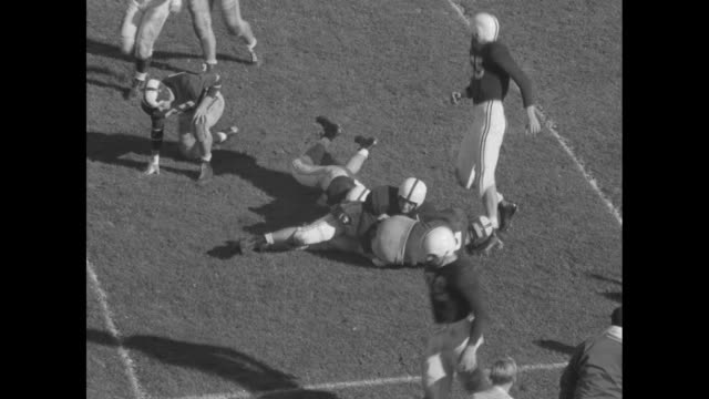 Title card Cornell vs Yale / VS football game / Yale player runs with ball fumbles Cornell's Ted Kolb falls on ball other players pile on top /...
