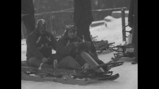 crash wrecks german bobsled on olympic run speeding down dangerous course at 65 miles an hour sleigh shoots off hairpin curve plunging into... - ボブスレーをする点の映像素材/bロール