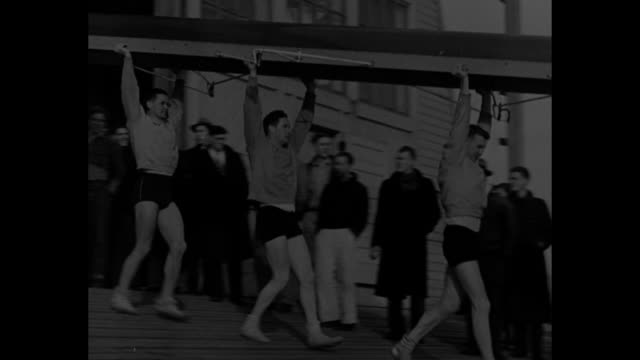 stockvideo's en b-roll-footage met crews hit 1938 pace / title card seattle wash / men from university of washington carrying boats to water / cu oarsman don hume / coach al ulbrickson... - universiteit van washington