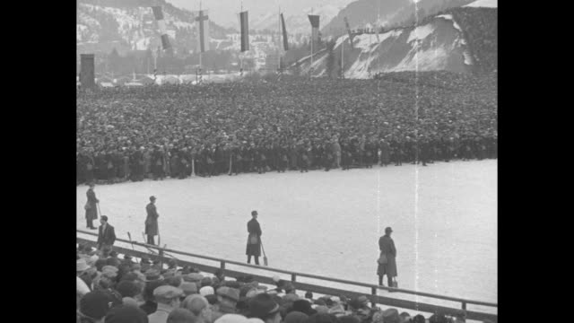 curtain falls on winter olympic games / crowd aerials of 1936 winter olympics in garmischpartenkirchen germany finals highlights / at ski arena... - bobsleighing stock videos & royalty-free footage