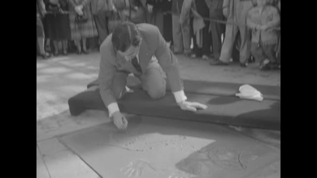 Danny Thomas Joins Court of Movie Fame superimposed over Thomas' hands above his signature in wet cement at Grauman's Chinese Theatre / WS pan down...