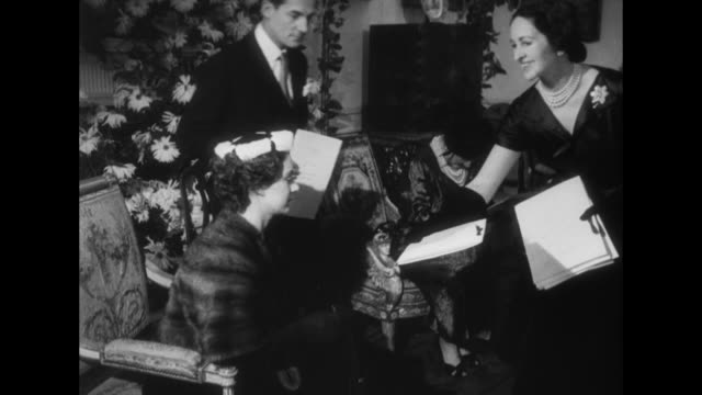 designers show fashions to queen mother superimposed over people in room / princess margaret with queen mother greet people in receiving line /... - princess margaret 1950 stock videos and b-roll footage