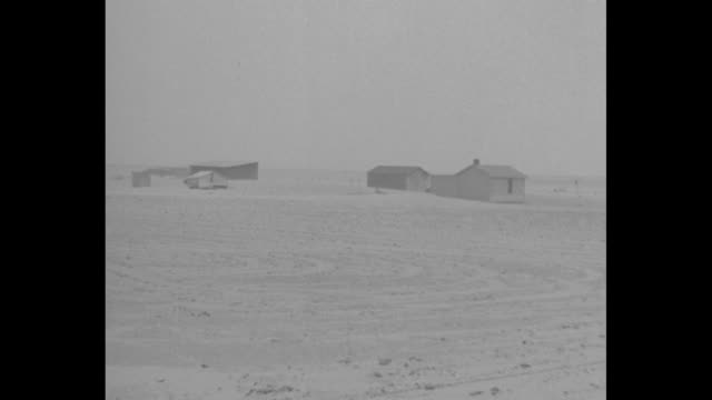 """vidéos et rushes de """"dust more dust"""" / three shots in dust storm of dust-covered fields / farmhouse surrounded by dust-covered field / shed with dust piled up against it... - phare de véhicule"""