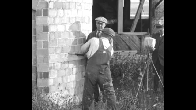 dynamite fells giant stack newport r i naval station workmen get set to raze useless brick chimney / workman pounding metal rod into hole in side of... - rod stock videos and b-roll footage