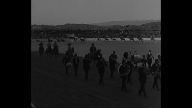 dynamite on hoof los angeles bareback and bruises balky steers and mustangs show tempers in clash with cowboys at livestock rodeo / marching band... - bocksprång bildbanksvideor och videomaterial från bakom kulisserna