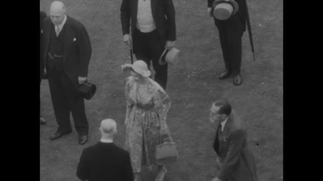 """title card """"elizabeth in scotland"""" / aerial crowd in circle on the grounds of holyroodhouse palace, queen elizabeth in small crowd in middle of... - ベルベット点の映像素材/bロール"""