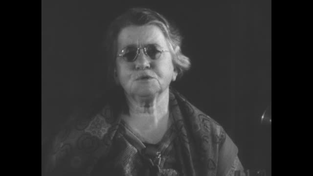 """stockvideo's en b-roll-footage met """"emma goldman in america - deported anarchist, once storm center between america and russia, returns after 15 years of exile"""" / goldman sits with... - city of neighbors: give once for all film title"""