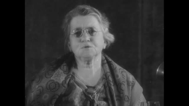 """stockvideo's en b-roll-footage met """"emma goldman in america! deported anarchist, once storm center between american and russia, returns after 15 years of exile"""" / emma goldman sits... - city of neighbors: give once for all film title"""