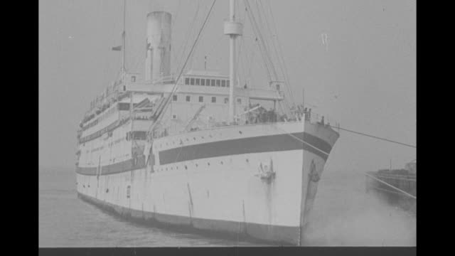 'England 8th Army wounded home from Africa' / pan down from mast of former luxury liner to WS the ship now requisitioned as a Red Cross hospital ship...