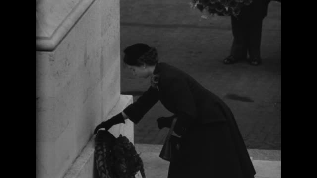 England Pays Homage to Her War Dead superimposed over soldiers in formation / Queen Elizabeth places a wreath at memorial / Clement Atlee Anthony...