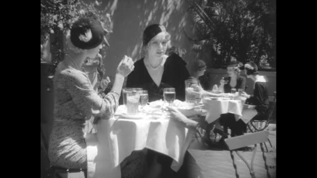 """new models slanting over eye are featured in retail millinery ass'n of america in advance autumn showing"""" / ladies dining at outdoor tables, wearing... - white点の映像素材/bロール"""