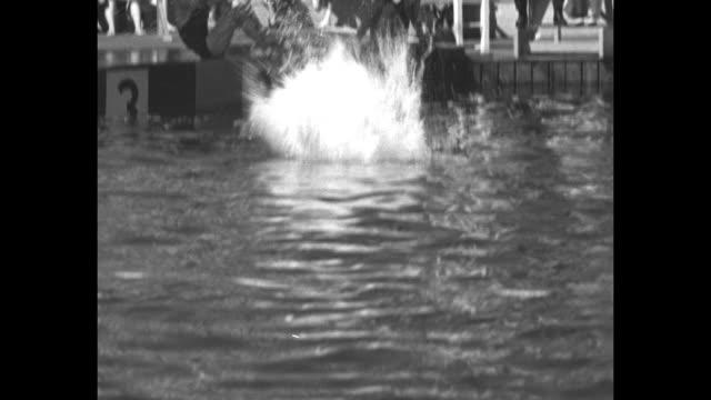 """fancy diving circus"" / big crowds at jones beach, swim deck in fg, people in water in bg, flag on flagpole / richard degener and marshall wayne... - diving platform stock videos & royalty-free footage"