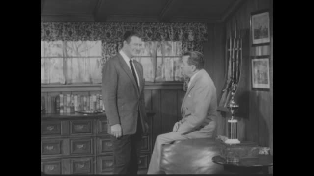 """fans name john wayne favorite star"" superimposed over actor john wayne, standing, speaking to ""hollywood reporter"" publisher w. r. wilkerson, seated... - wochenschau stock-videos und b-roll-filmmaterial"