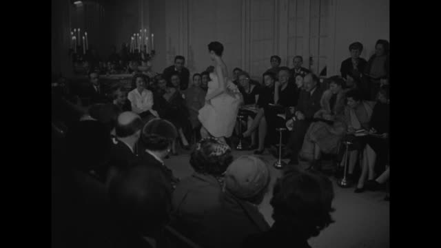 title card fantastic fashions superimposed on runway model / vs woman raises skirt to show garters with jeweled clip audience members' right profile... - straw hat stock videos and b-roll footage