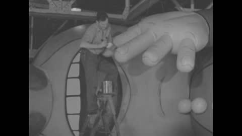 """vídeos y material grabado en eventos de stock de """"fantasy - artists create balloon comics"""" / a warehouse facility with an inflated globe, a large rubber body; one lying as a man raises a smaller one... - torso"""