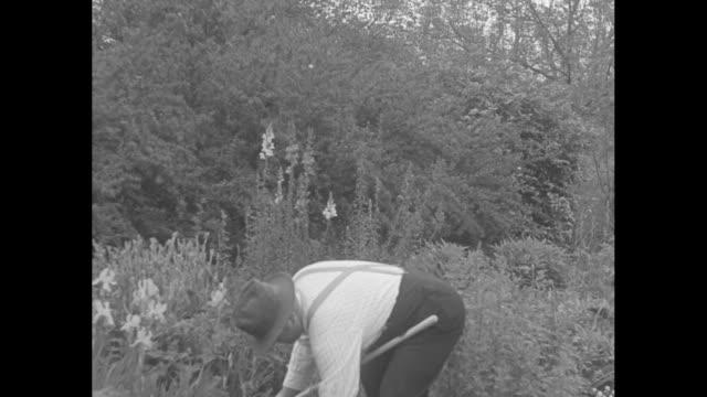 "vídeos de stock, filmes e b-roll de ""farmer brown on tour!"" / sam brown hoeing in garden / men carrying gas cans walking past camera / men walk up to brown hoeing in garden, he stops... - 1930"