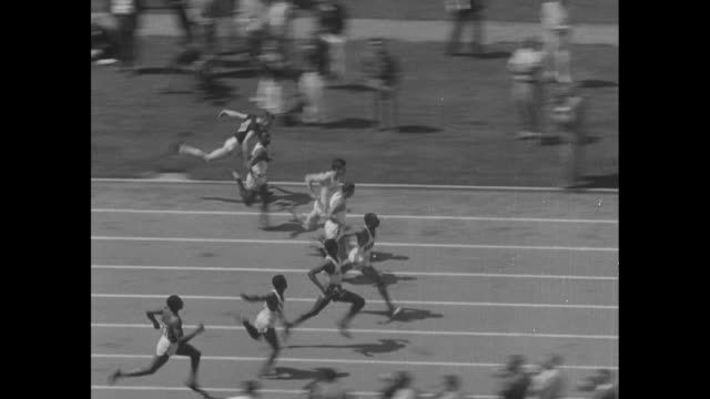 Final Olympic Tryouts superimposed over rear shot man fires starting pistol for race / spectators in stands at Los Angeles Memorial Coliseum during...