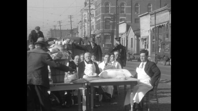 food for jobless omaha neb citizens pay grub fines in street court to help needy / men wearing aprons sit at table as people place crop foods on... - great depression stock videos & royalty-free footage