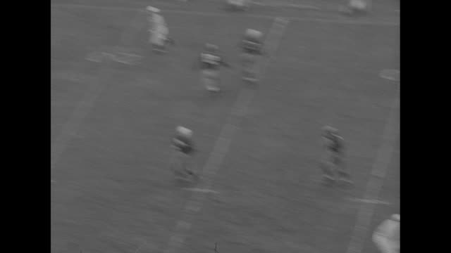 'Football Harvard Vs Yale' superimposed over football game / VS football game spectators man in hat waves to camera touchdown people run out onto...