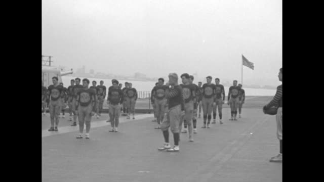 """""""football lid off as tars train at sea! navy's floating gridiron candidates hold first drill on uss saratoga"""" / midshipmen football players run... - practice drill stock videos & royalty-free footage"""