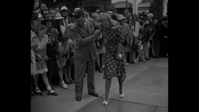 """""""footsteps: fame in concrete for ginger rogers"""" / actress/dancer ginger rogers leans on arm of the manager of grauman's chinese theatre as she steps... - tcl chinese theatre stock videos & royalty-free footage"""