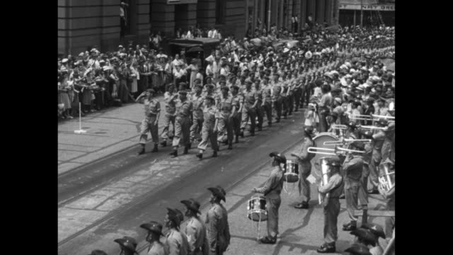 vídeos de stock, filmes e b-roll de for korea nz troops parade through brisbane / vs new zealand army soldiers march thru crowd of applauding and flag waving civilians military band... - cross legged