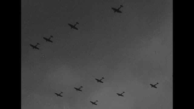 for valor battle of britain day honors raf / royal air force ensign flutters in breeze / far planes fly in formation / battle of britain day parade... - luftschlacht um england stock-videos und b-roll-filmmaterial