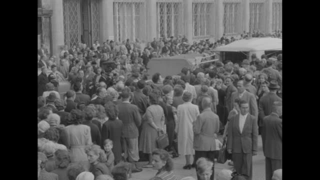 foreign news / title food crack iron curtain in berlin superimposed over crowd / east germans crowd streets to receive food relief near border of... - 1953 stock videos & royalty-free footage