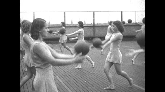 'Frauleins use rhythm to keep girlish figures Pupils of Medau school in Berlin Germany try musical exercise with medicine balls' / VS pairs of women...