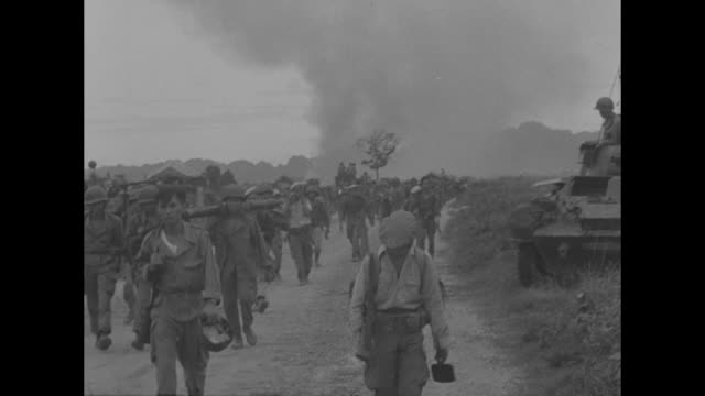 stockvideo's en b-roll-footage met french slow red tide in fierce fighting superimposed over grassy field and mountains in indochina / ws sun breaks through holes in clouds shines on... - 1954