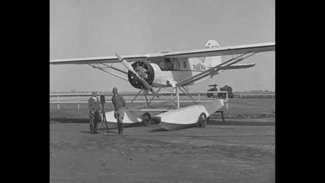'Girl to Fly Ocean New York Petite Beryl Hart and copilot Lieut MacLaren prepare for first flight over Atlantic carrying freight' / WS aviators Beryl...