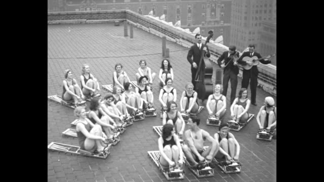 """girls muscle in on skyline racket - new york chorines keep those svelte night club figures by exercising on hotel biltmore roof"" / three shots of... - exercise machine stock videos & royalty-free footage"
