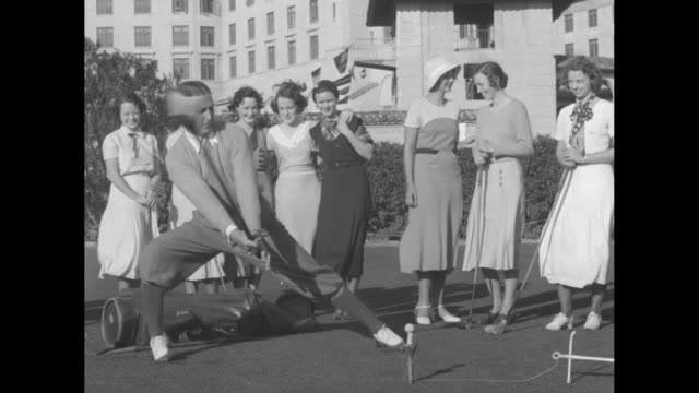 golf suits him to a tee joe kirkwood of miamibiltmore club tries some new trick shots / kirkwood standing with clubs surrounded by group of women and... - golf swing women stock videos & royalty-free footage