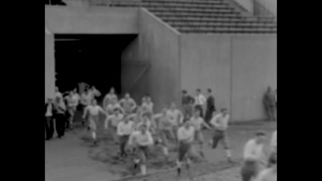 Grid Warriors in Training Pittsburgh Coach Southerland puts Pitt Panthers through workout / VS Pitt Panthers football team members run from tunnel...