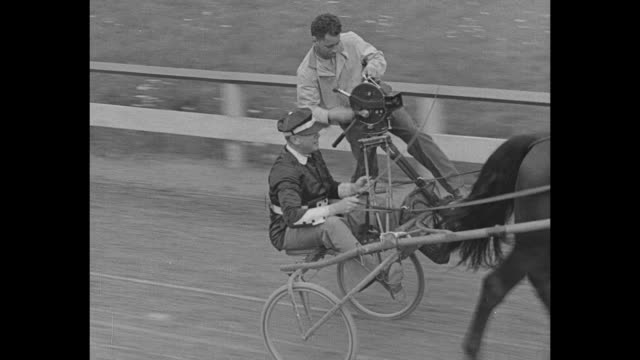 """harness filly wins $20,000 in a trot"" / title: ""goshen, n. y."" superimposed over crowd in midway area of good time park, site of the hambletonian... - träns bildbanksvideor och videomaterial från bakom kulisserna"