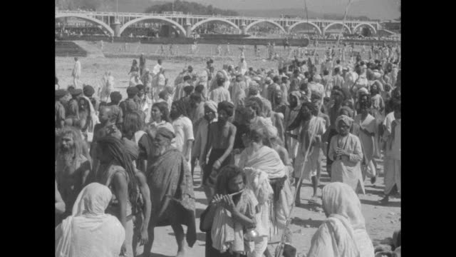 hindus wash sins away in sacred river superimposed over extremely wide crowd shot / hindus standing along banks of river which is in the foreground... - lotus position stock videos & royalty-free footage