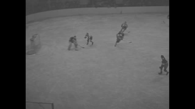 'Hockey in Full Swing' / title superimposed on hockey rink 'New York' / VS high angle views of game between New York Americans in light jerseys and...