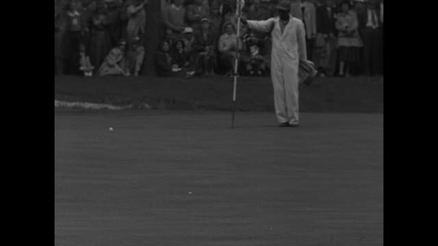 hogan wins masters golf superimposed over crowd shot / long shot of crowd on green then pan up to treetops / pan along ground to flag and ball on... - plakette stock-videos und b-roll-filmmaterial
