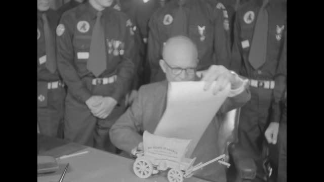"vídeos de stock e filmes b-roll de ""ike greets boy scouts on birthday "" / eisenhower at his desk unrolling a scroll, boy scouts behind him. the scouts, who are in uniform, gave the... - associação de escoteiros"