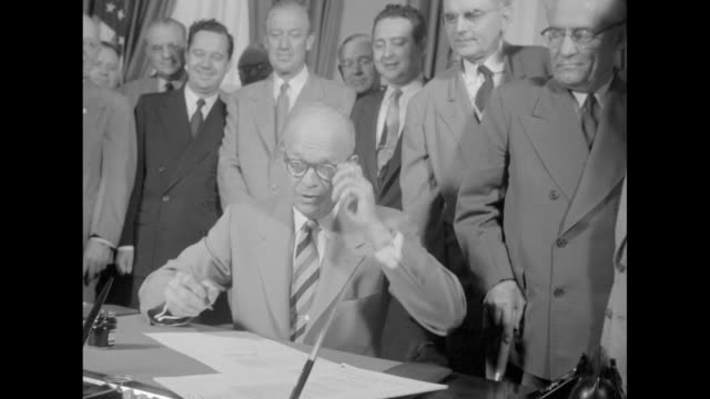 vídeos de stock, filmes e b-roll de ike signs tidelands oil bill superimposed over ws president eisenhower at his oval office desk signing bill / ws eisenhower puts pen down takes... - dwight eisenhower