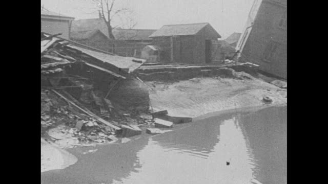 """vídeos de stock e filmes b-roll de """"in 1913, serious floods swept dayton, ohio, causing a small loss of life but property damage of over two billion dollars"""" / pan across flooding... - water's edge"""
