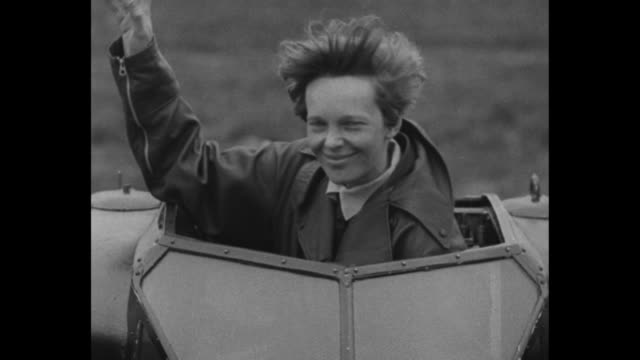 In 1932 Aviation Goes Ahead Amelia Earhart proves a lone woman can fly the Atlantic / Earhart waving before sitting down in cockpit and sliding top...