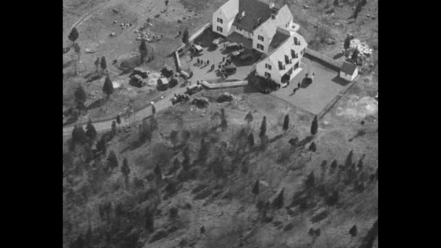 In 1932 The World Weeps Baby Lindbergh murdered a kidnapper eludes justice / aerial view Lindbergh mansion / probably reporters wearing hats crowded...