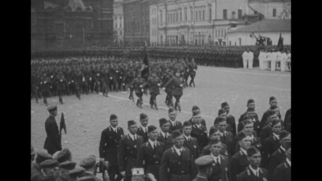 title card in cyrillic script / soviet may day military parade / marching troops salute / four male spectators watching one shouting enthusiastically... - cyrillic script stock videos & royalty-free footage